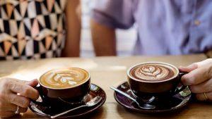 Two seniors share coffee.