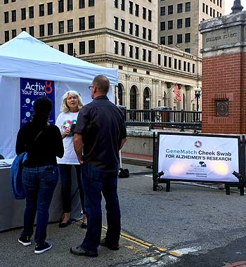 Dr. Karen Bell, a volunteer with the Memory and Aging Program at Butler Hospital, talks with people about Alzheimer's research at a September, 2018 Waterfire event in Providence, Rhode Island.